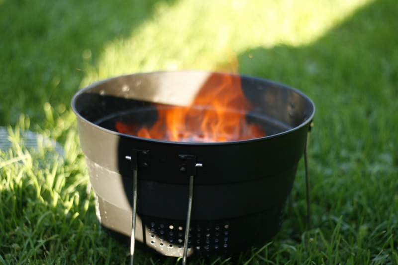 Foto av en liten grill uten rist, med åpen flamme.