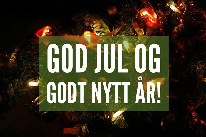 """Et nærbilde av et juletre med hjerteformede, små """"lamper"""" og små, elektroniske juletrelys. Bildet er mørkt og kun opplyst av det røde og gule lyset, noe som skaper en lun stemning. Over bildet er en delvis gjennomsiktig, mosegrønn rektangulær boks med hvit skrift i store bokstaver der det står """"God jul og godt nyttår!"""" i caps lock."""