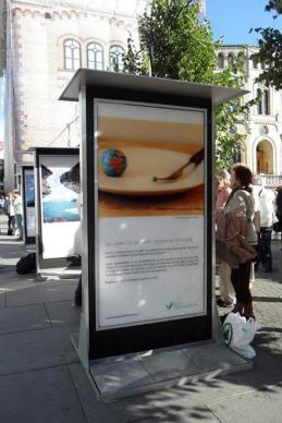 Fotografi av en rekke plakater på omtrent 2 meter stående langs Karl Johan, like ved Stortinget. Forrest er en plakat med et bilde av en asjett, en gaffel og en liten jordklode. På gaffelen som ligger på tallerkenen, er en liten, grønn ert Det er en solskinnsdag, og det står noen mennesker til høyre i bildet og ser på plakatene. Under plakaten er det en tekst. Les resten av blogginnlegget for å få opplest hva som står på plakaten (man kan ikke se det på bildet).