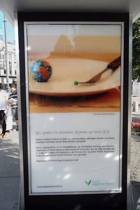 Fotografi (halvnært bilde) av en av mange plakater på omtrent 2 meter stående langs Karl Johan, like ved Stortinget. Forrest er en plakat med et bilde av en asjett, en gaffel og en liten jordklode. På gaffelen som ligger på tallerkenen, er en liten, grønn ert Det er en solskinnsdag, og det står noen mennesker til høyre i bildet og ser på plakatene. Under plakaten er det en tekst. Les resten av blogginnlegget for å få opplest hva som står på plakaten (man kan ikke se det tydelig på bildet).